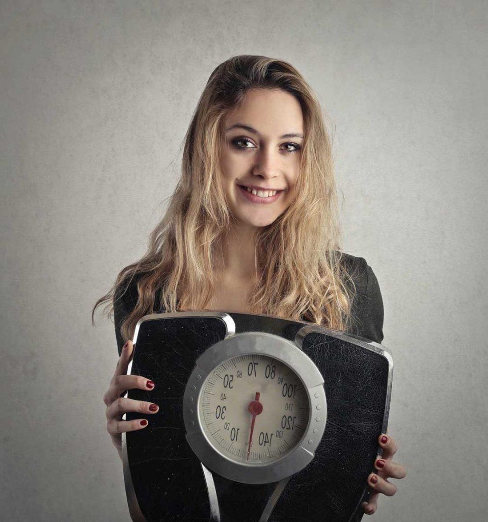 Une femme avec une balance dans les mains car elle souhaite perdre du poids