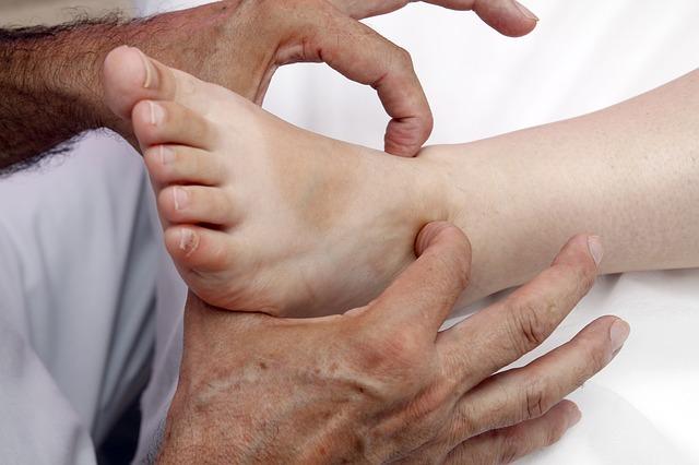 Un praticien entrain de faire de la réflexologie plantaire sur un pied
