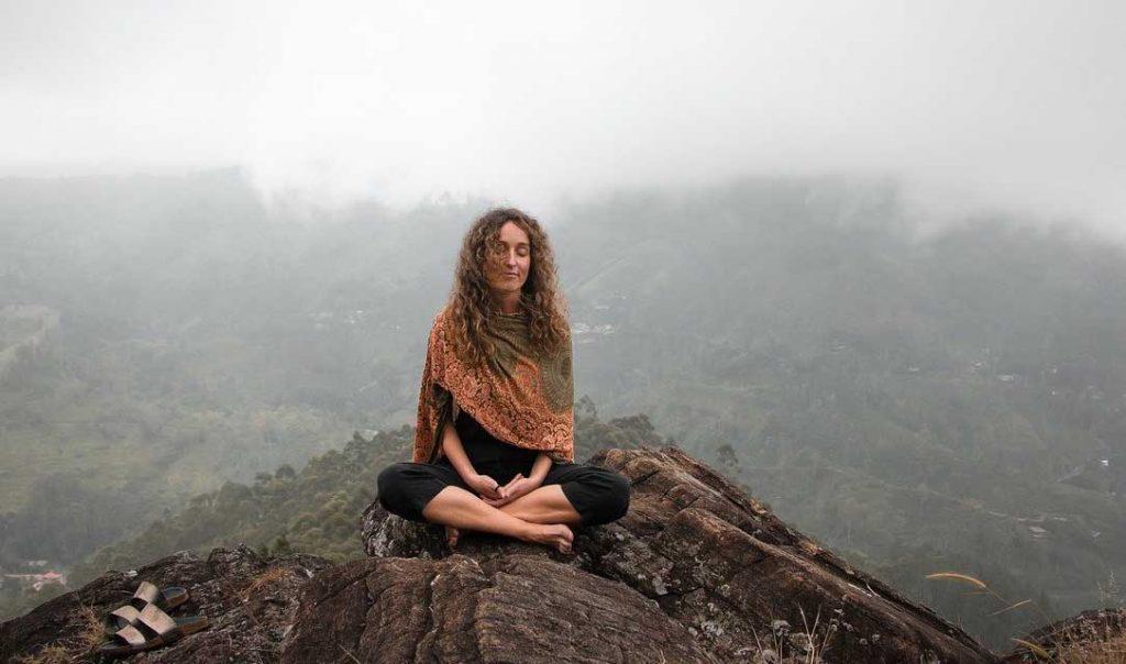 une femme qui médite sur un rocher